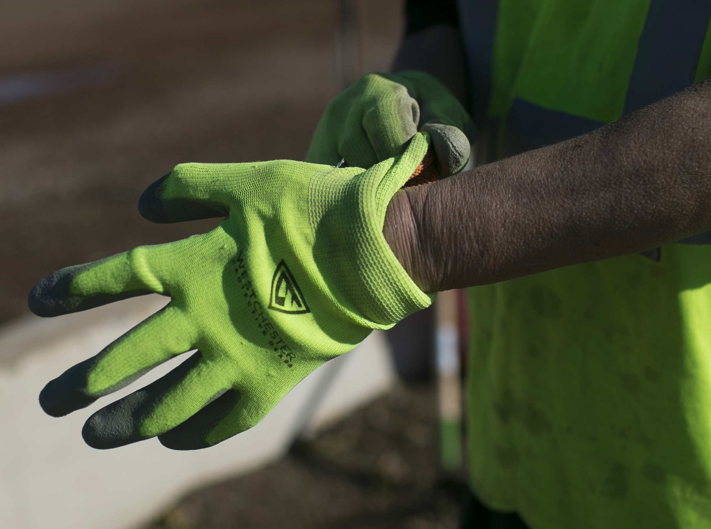 Sherry Millegan pulls on gloves to help clean Grand Canal Linear Park as part of the Phoenix Rescue Mission's Glendale Works program on Jan. 7, 2019 in Glendale, Arizona.