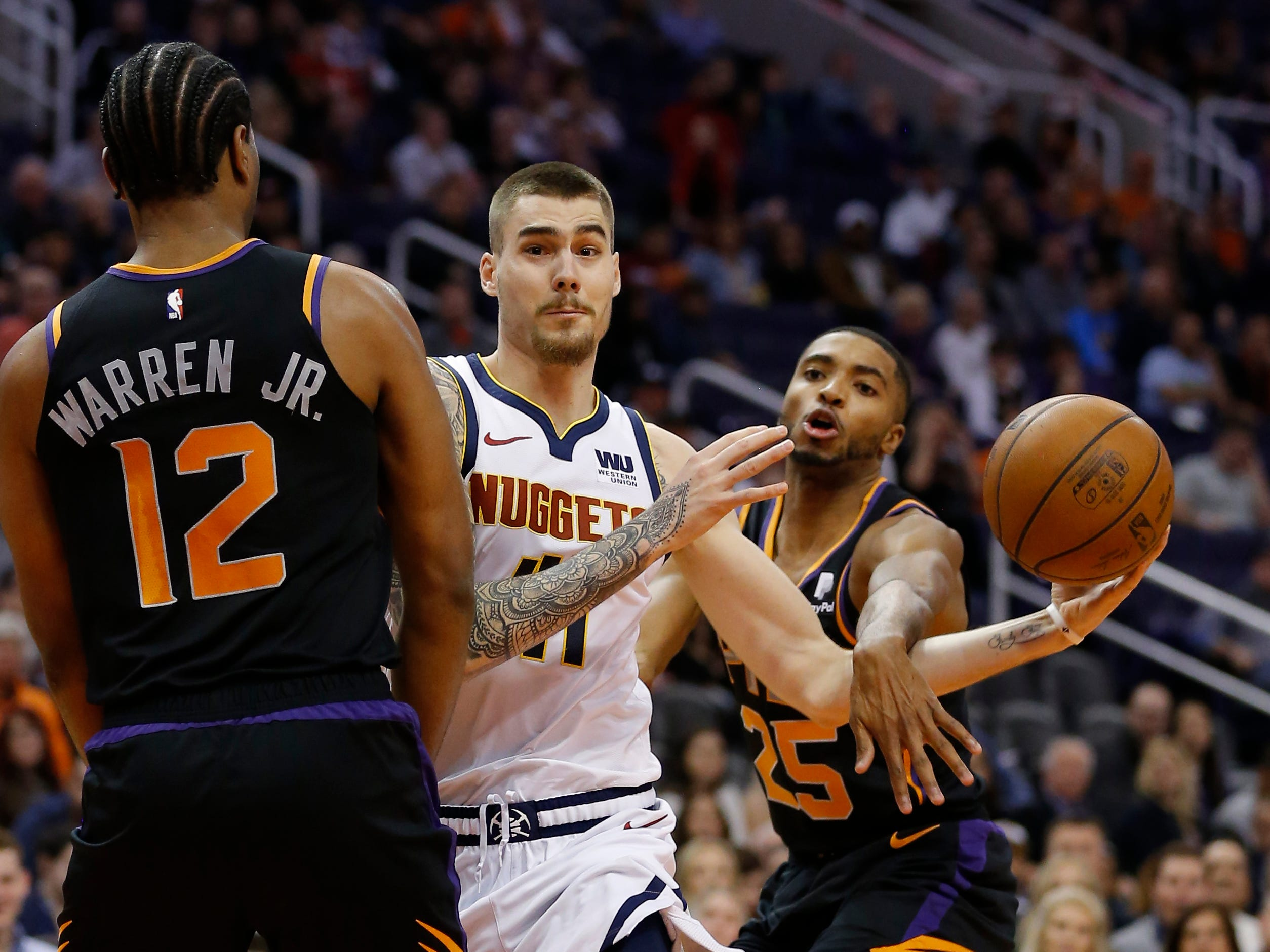 Denver Nuggets forward Juan Hernangomez (41) gets fouled while driving between Phoenix Suns forward T.J. Warren (12) and Mikal Bridges (25), Saturday, Jan. 12, 2019, in Phoenix. (AP Photo/Rick Scuteri)