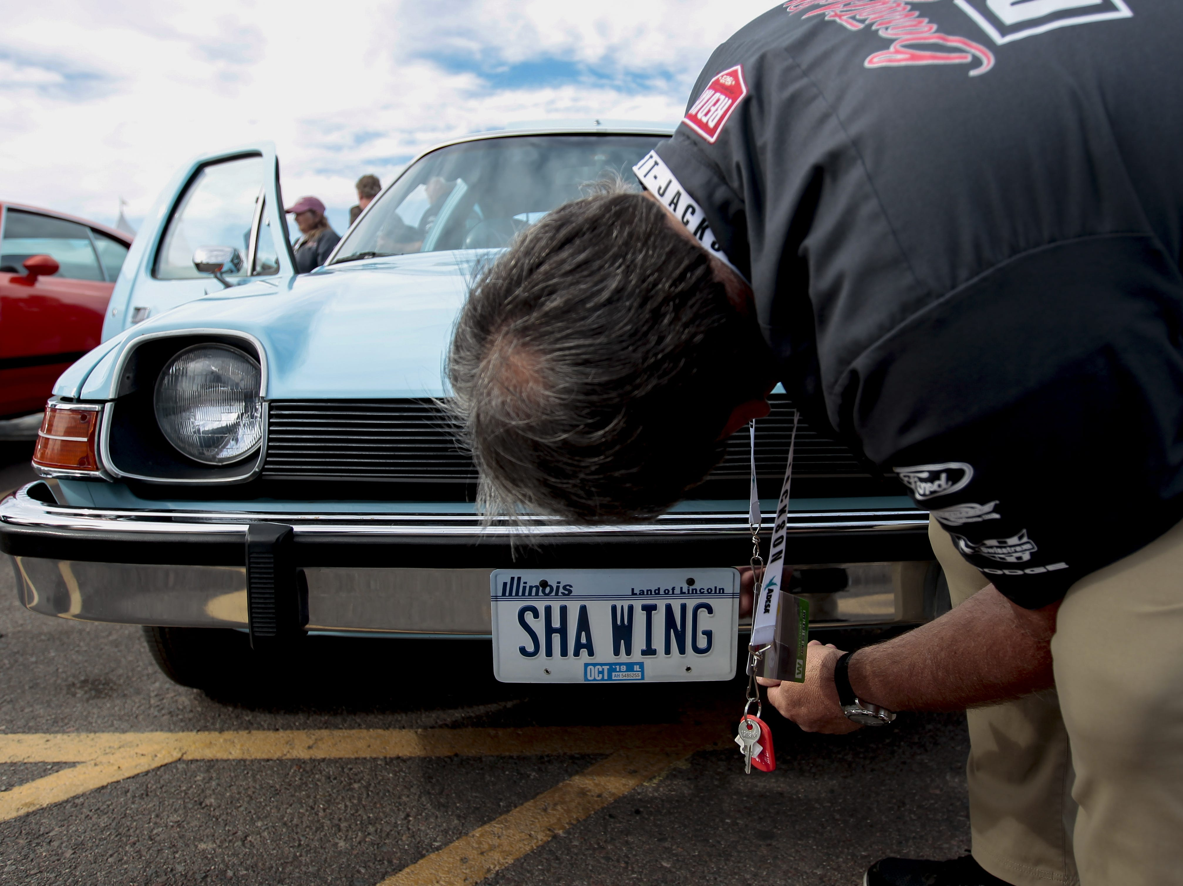 A Barrett-Jackson driver looks at the license plate of a recreation of the Mirthmobile from Wayne's World at the car auction on Jan. 12.