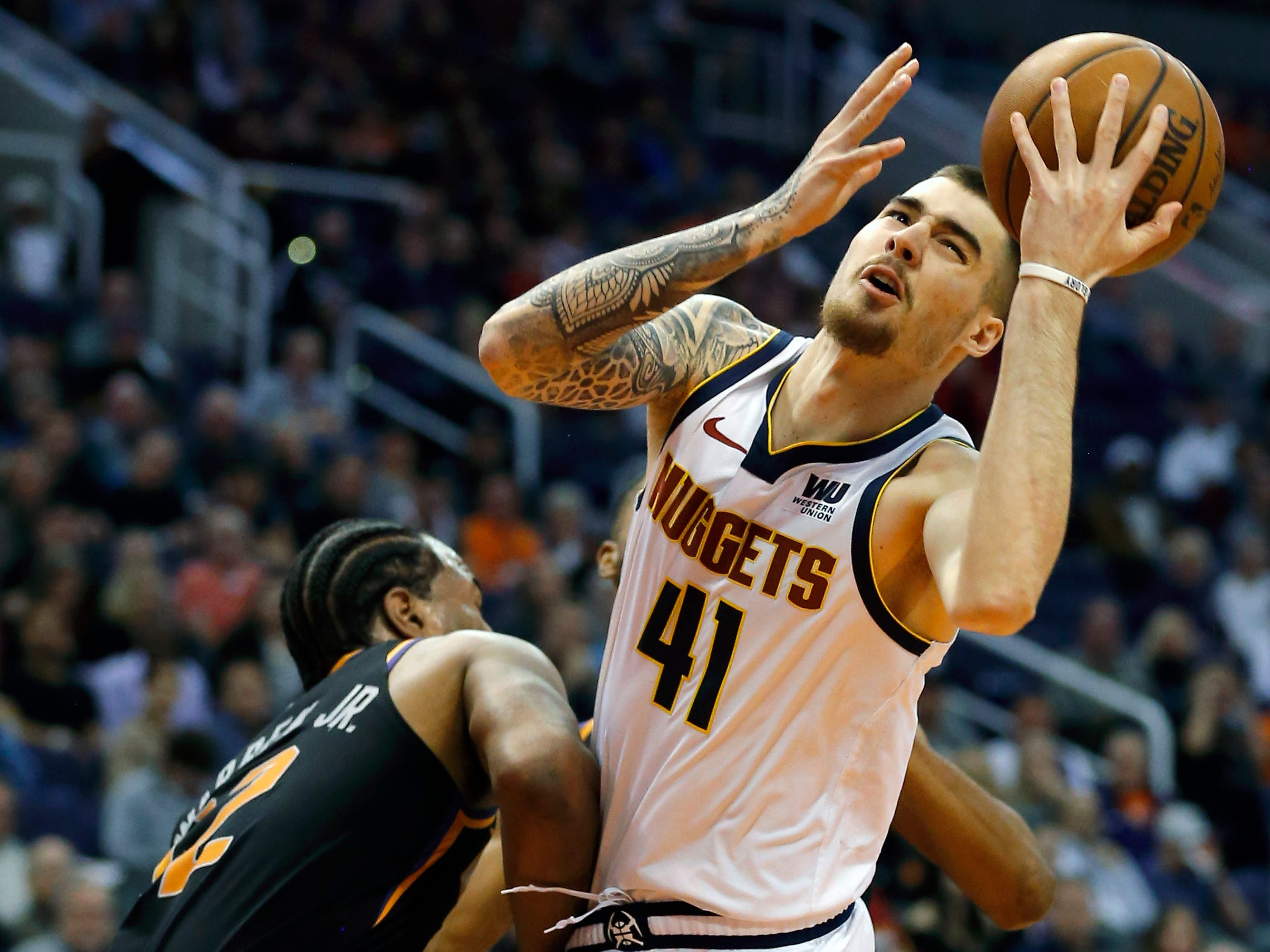 Denver Nuggets forward Juan Hernangomez (41) drives on Phoenix Suns forward T.J. Warren, Saturday, Jan. 12, 2019, in Phoenix. (AP Photo/Rick Scuteri)