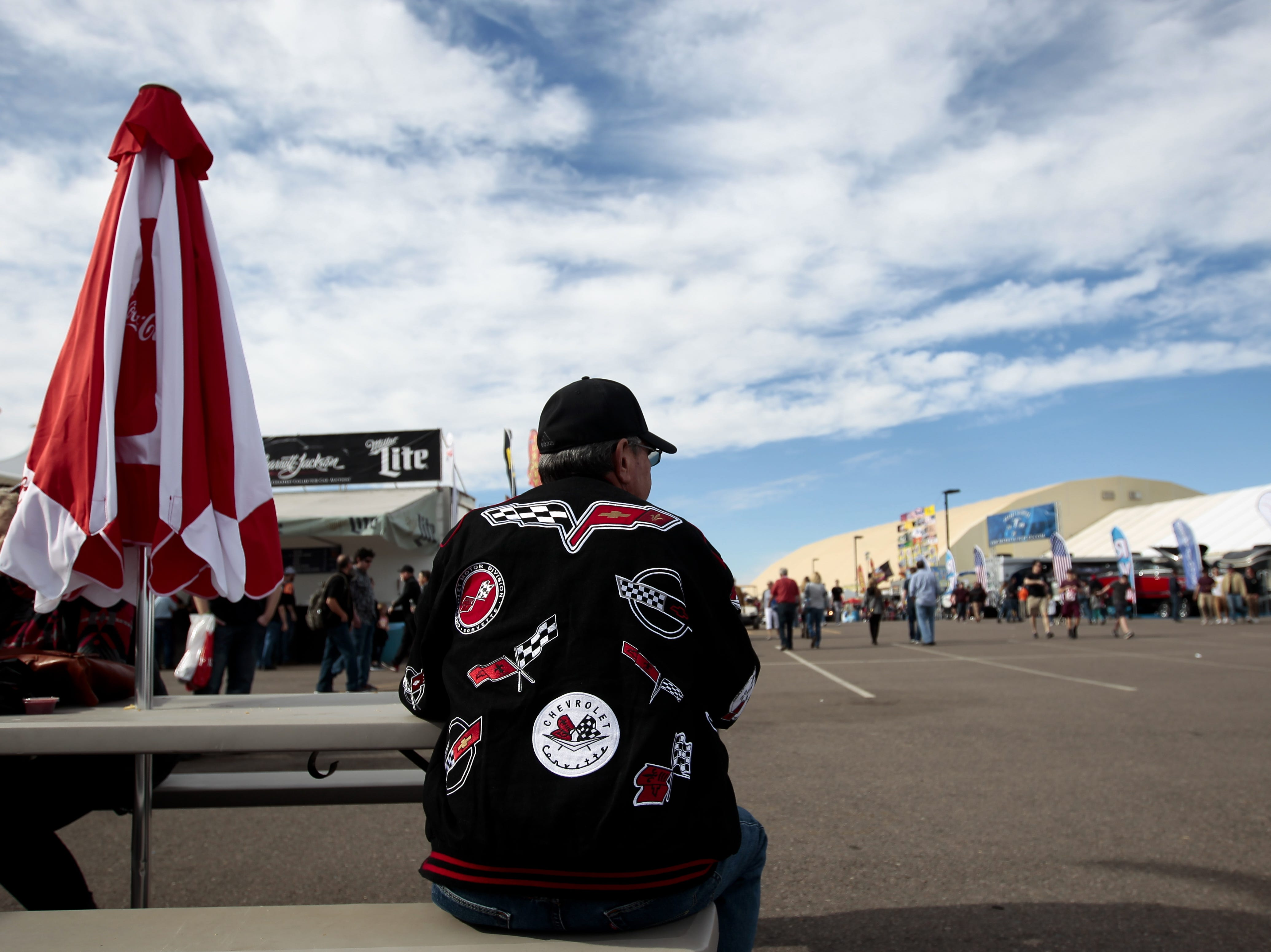 A man sits outside a food vender at the Barrett-Jackson Car Auction on Jan. 12, the first day of the event.