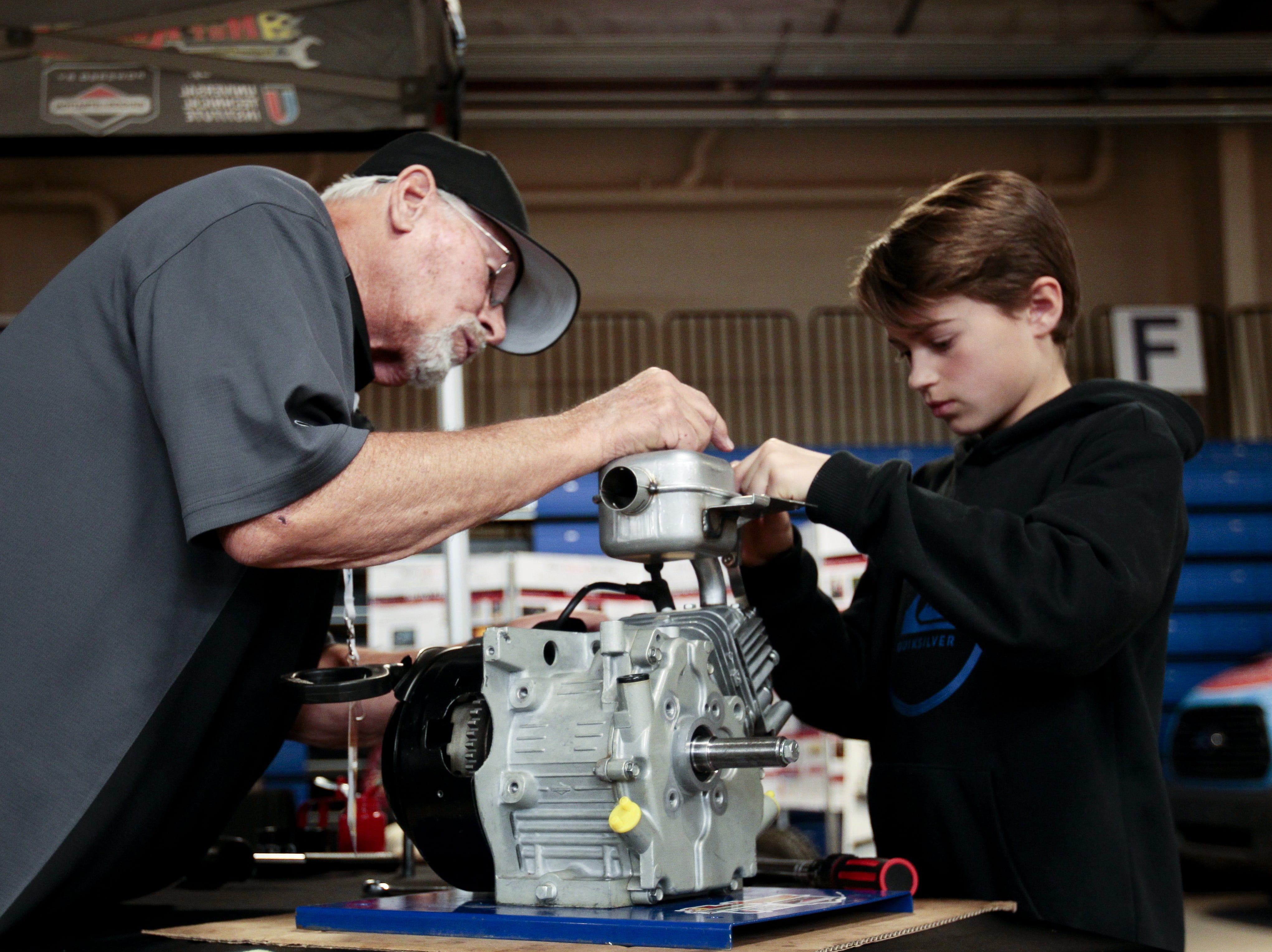 Jacob Fagan, 11, completes the engine challenge at a booth run by the Hot Dodders of Tomorrow in the kids area of the Barrett-Jackson Car Auction on Jan. 12. Rich Ralstin, left, helps explain the engine.