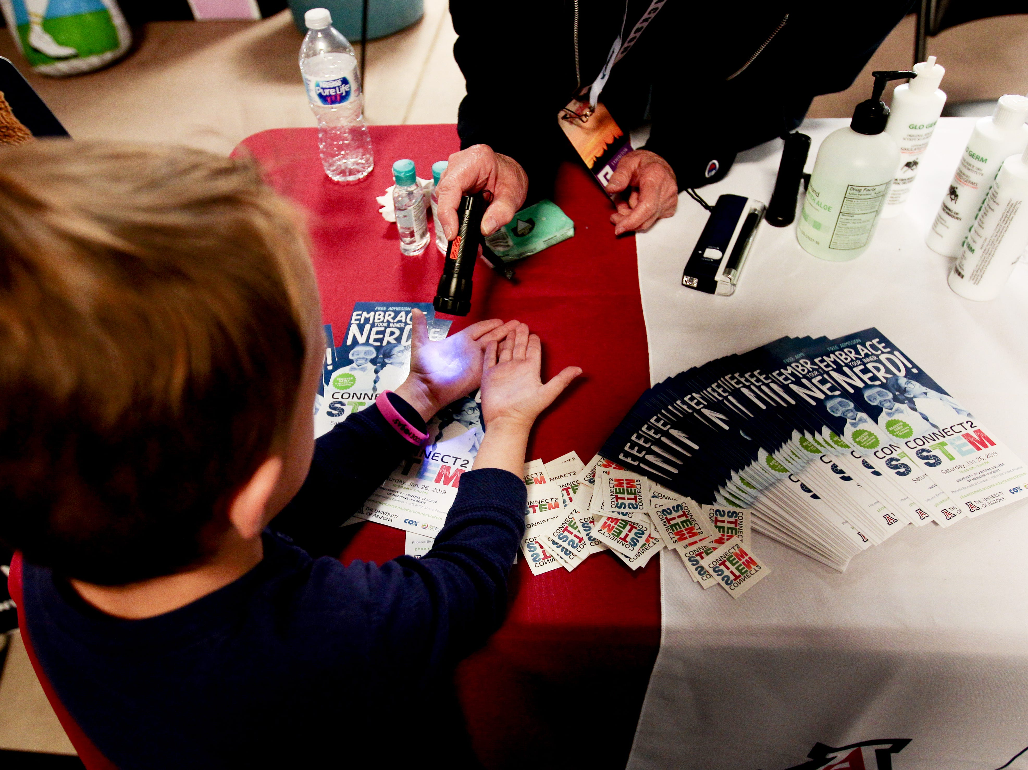Leo Breen-Harris, 5, has his hands scan with a light to expose germs at a stand run by students from the University of Arizona College of Medicine in the kids area of the Barrett-Jackson Car Auction on Jan. 12.