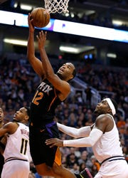 Phoenix Suns forward T.J. Warren (12) drives past Denver Nuggets forward Paul Millsap in the second half, Saturday, Jan. 12, 2019, in Phoenix. (AP Photo/Rick Scuteri)
