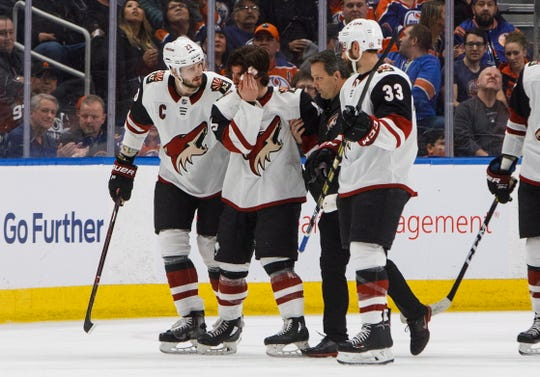 Arizona Coyotes' Conor Garland (83) is helped off the ice after taking a puck to the head during the second period against the Edmonton Oilers on Saturday, Jan. 12, 2019, in Edmonton Alberta. (Jason Franson/The Canadian Press via AP)