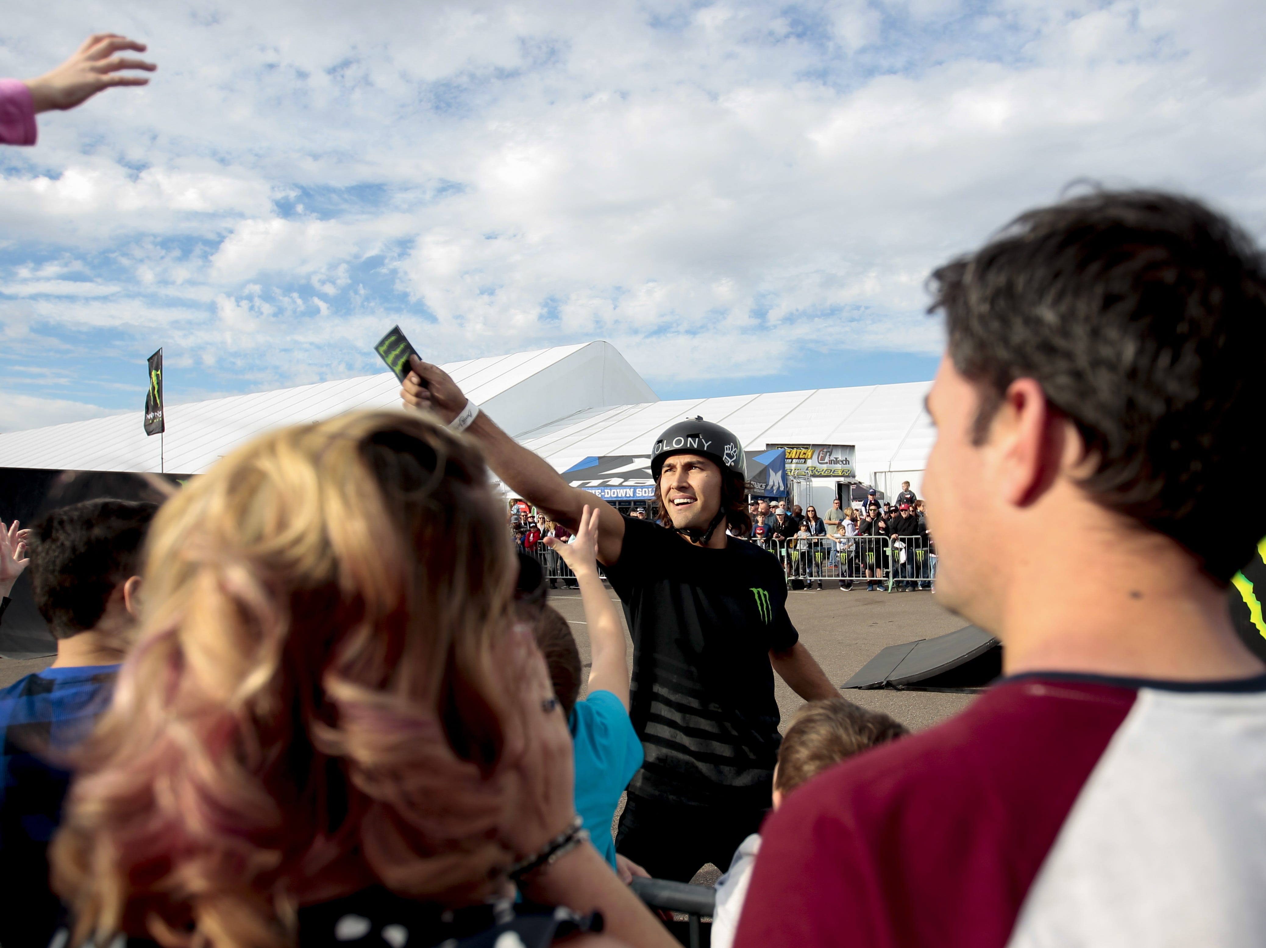 Members of the Monster Energy BMX team hand out stickers to fans that are the loudest at the Barrett-Jackson Car Auction on Jan. 12, the first day of the event.