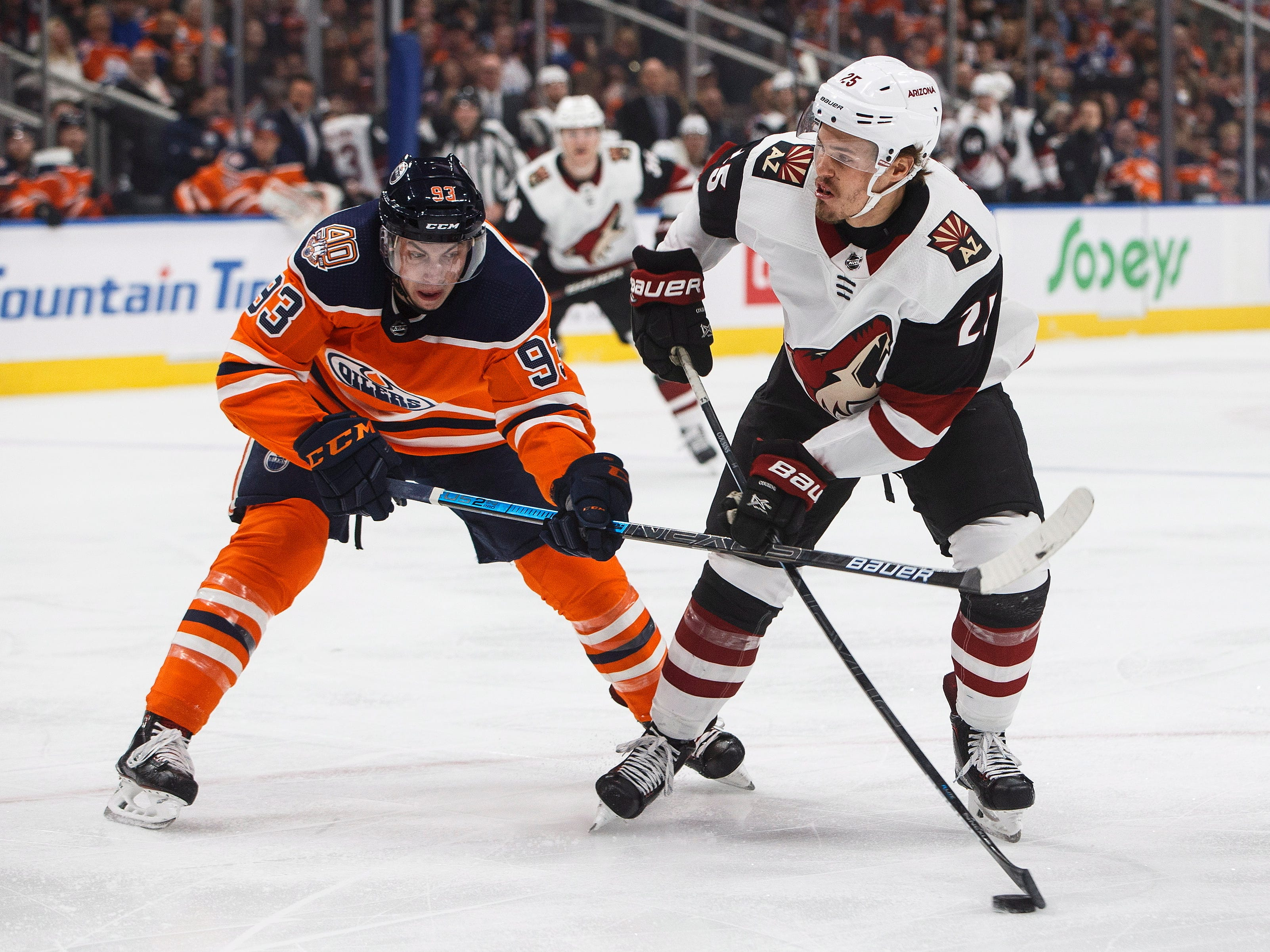 Arizona Coyotes ' Nick Cousins (25) is chased by Edmonton Oilers' Ryan Nugent-Hopkins (93) during the first period, Saturday, Jan. 12, 2019, in Edmonton Alberta. (Jason Franson/The Canadian Press via AP)