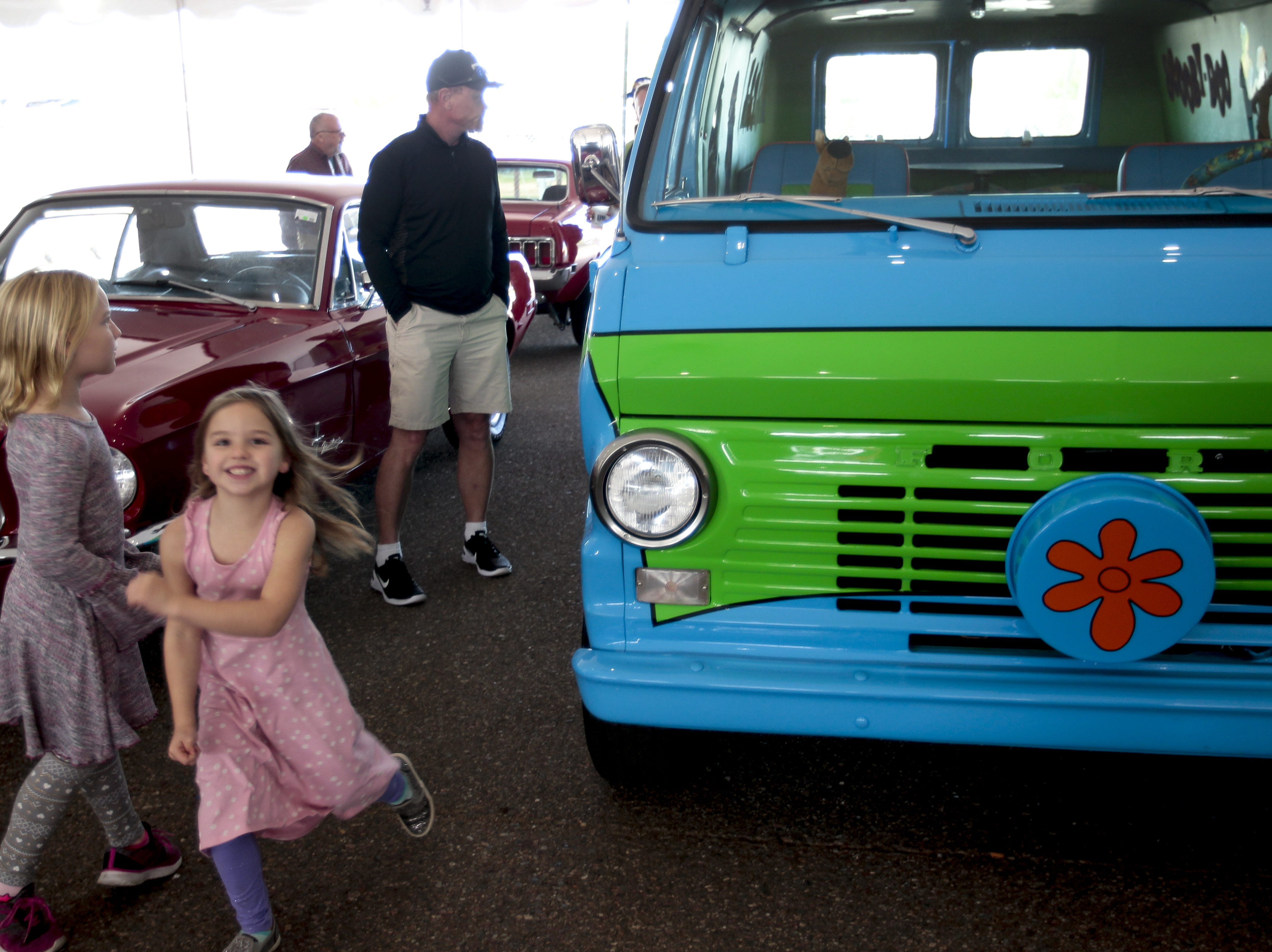 Kids run around a van that has been remodeled to look like  at the Mystery Machine from Scooby Doo at the Barrett-Jackson Car Auction on Jan. 12, the first day of the event.