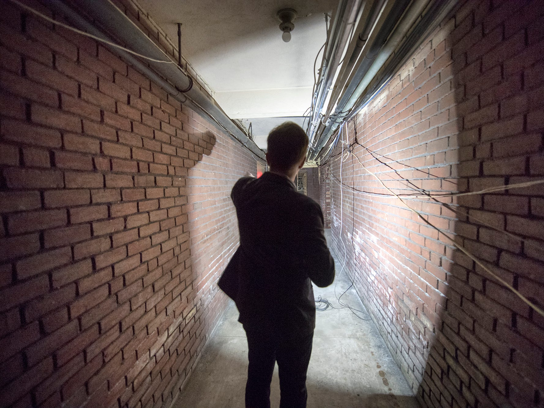 Dylan Bauer, president of development for Royal Square Development & Construction, walks through a narrow hallway that runs the length of the basement of the former Cobblestones Building on Wednesday January 9, 2019.