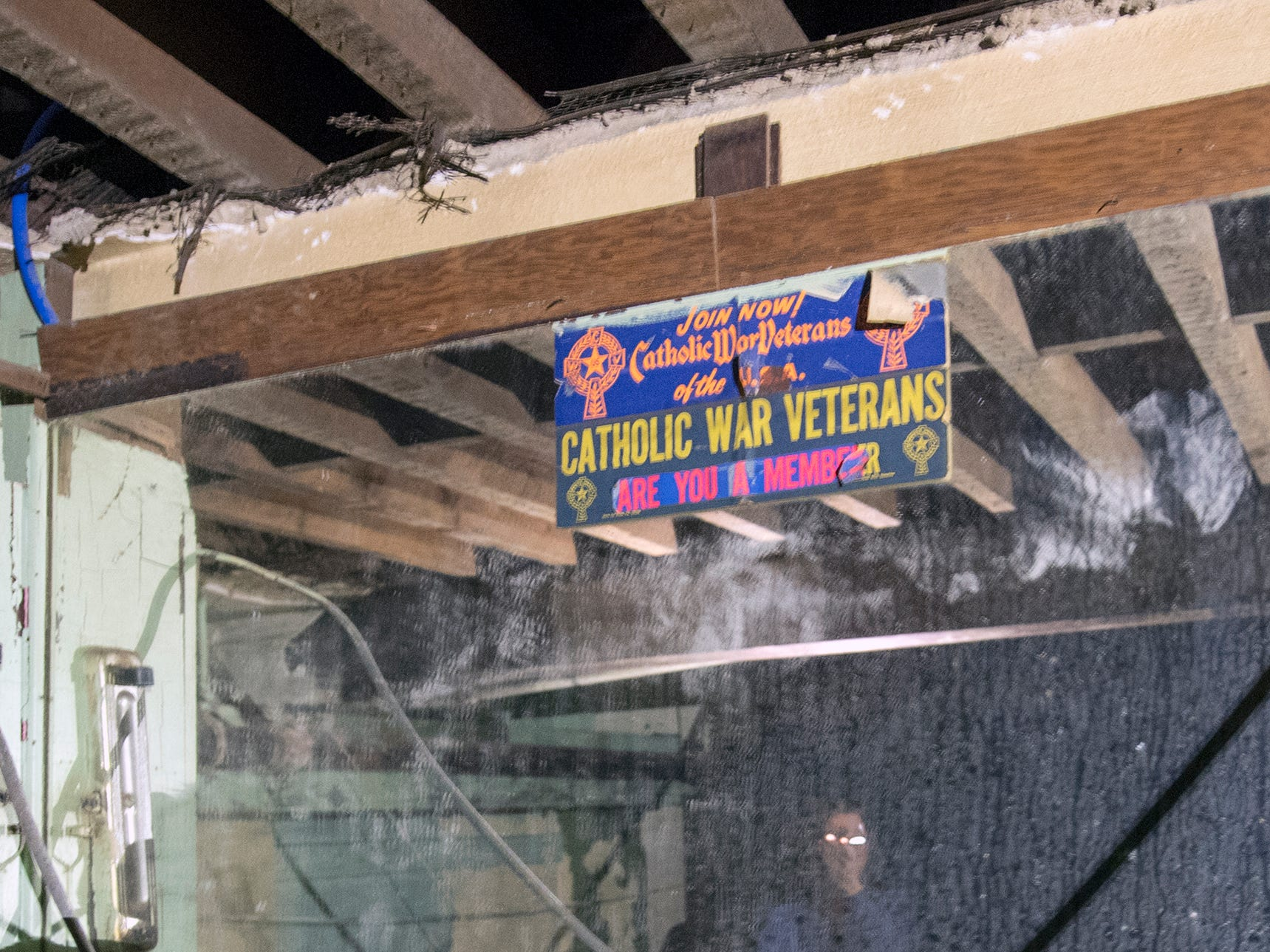 "A sign on a mirror reads ""Join Now! Catholic War Veterans of the U.S.A. Are You a member"" is seen above a basement bar that dates back to when the building was a Knights of Columbus hall."