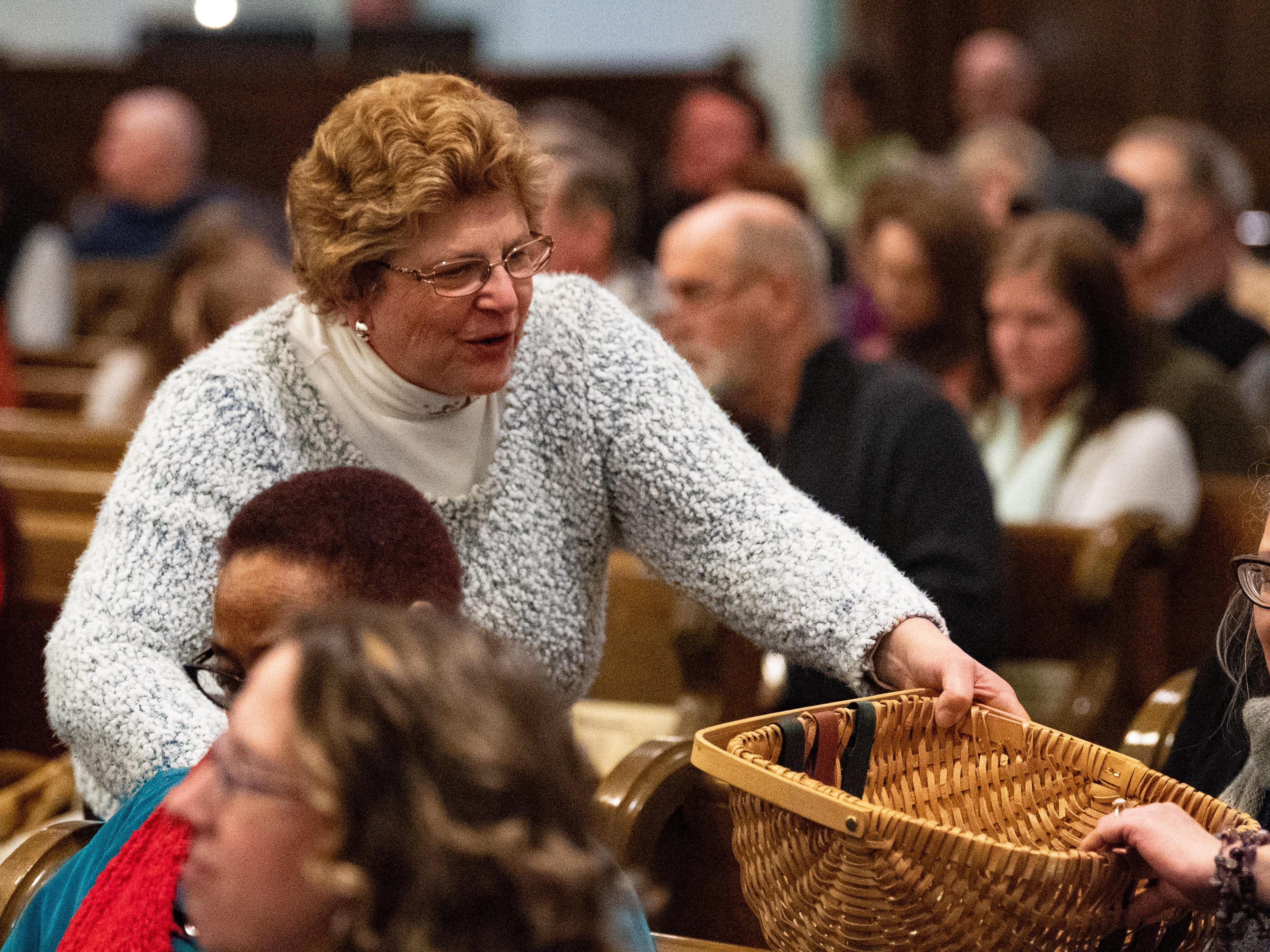Near the end of the concert, members of the church pass around a basket collecting offerings during the 21st annual Jazz Vespers concert at First Presbyterian Church in York, January 12, 2019.