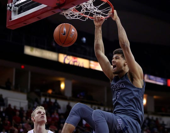 Nevada's Trey Porter dunks over Fresno State's Sam Bittner during Saturday's Mountain West game in Fresno.