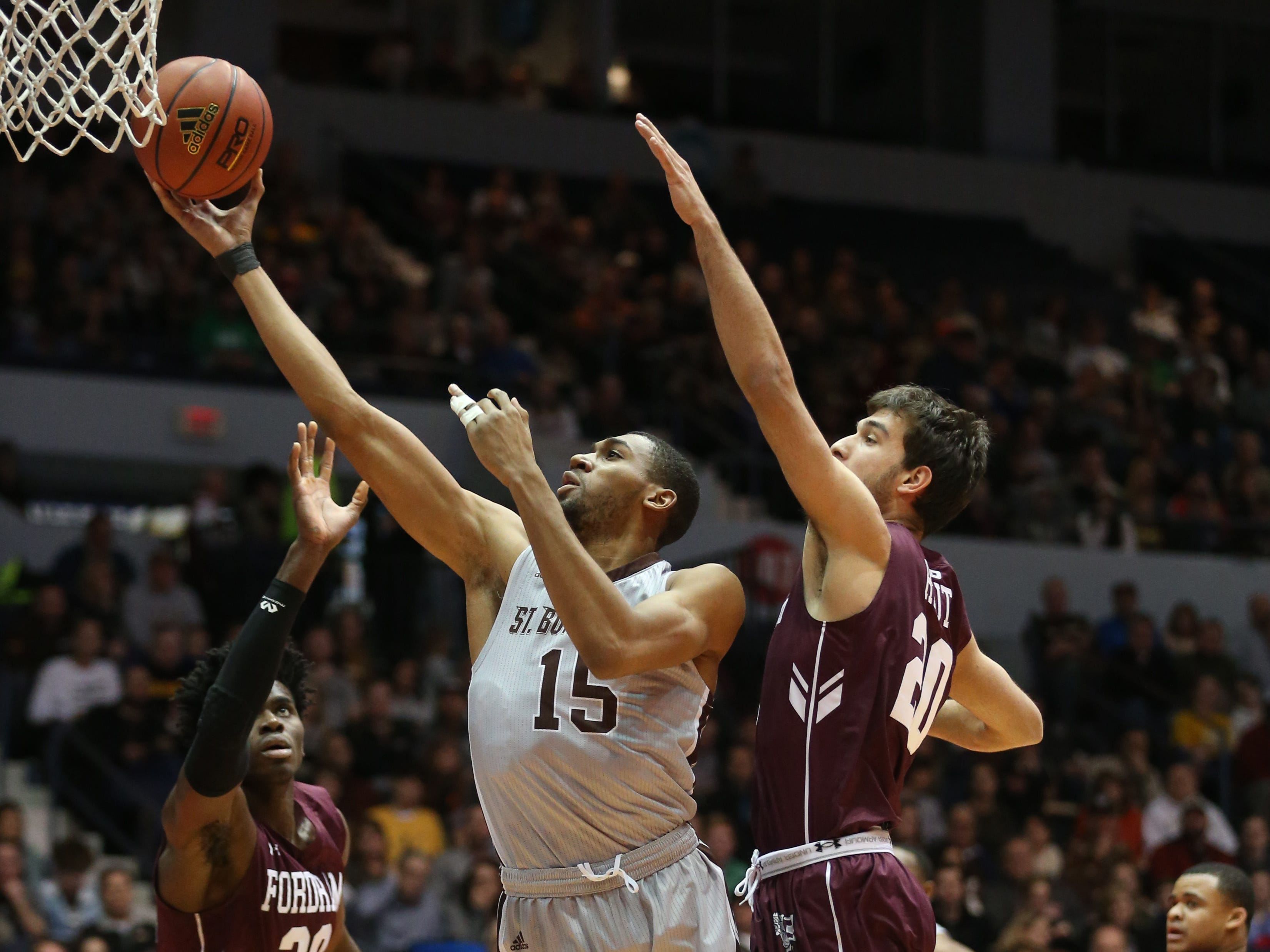 St. Bonaventure's LaDarien Griffin puts in two points between the defense of Fordham's Ivan Raut, right, and Onyi Eyisi, left.