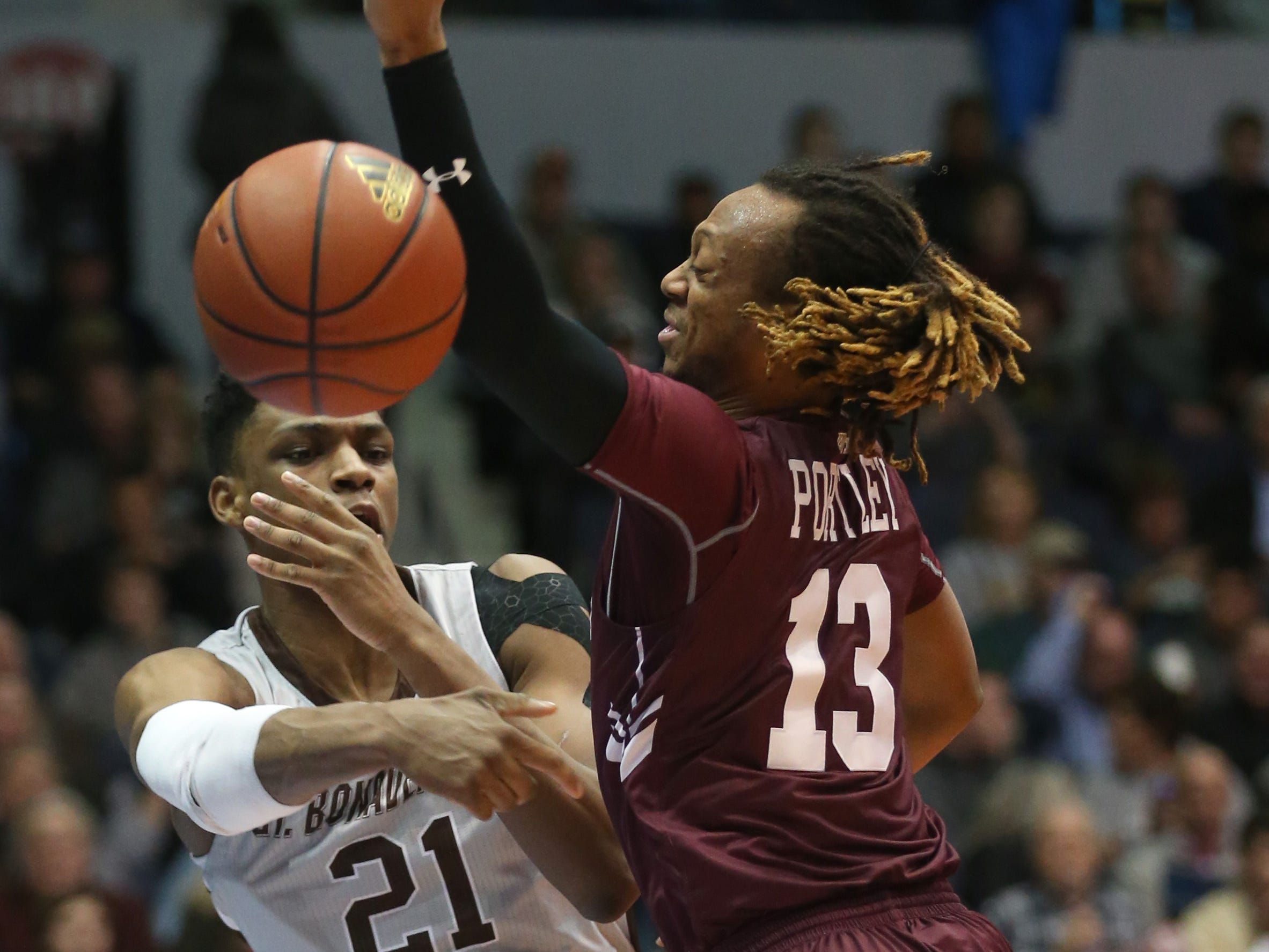 St. Bonaventure's Osun Osunniyi, left, makes a leaping save of the ball, passing it to a teammate around Fordham's Antwon Portley, before going out of bounds.