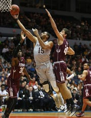 St. Bonaventure's LaDarien Griffin lays in two points between the defense of Fordham's Ivan Raut, right, and Onyi Eyisi, left, during their game at the Blue Cross Arena in Rochester Saturday, Jan. 12, 2019.  The Bonnies won the game 71-44.