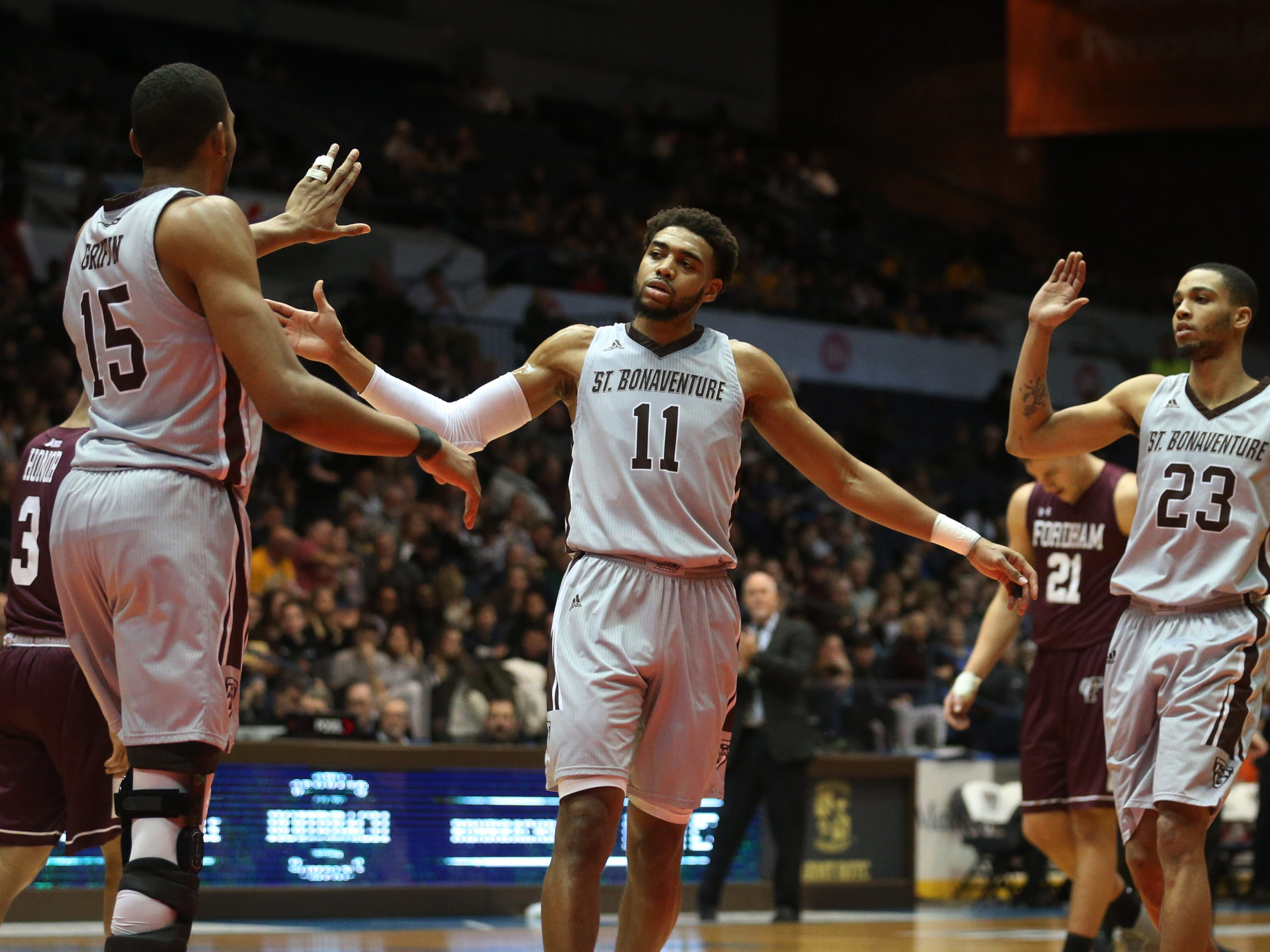 St. Bonaventure's LaDarien Griffin, left, celebrates with teammates Courtney Stockard, center, and Jalen Poyser, right, after getting the bucket and the foul on Fordham in the first half.