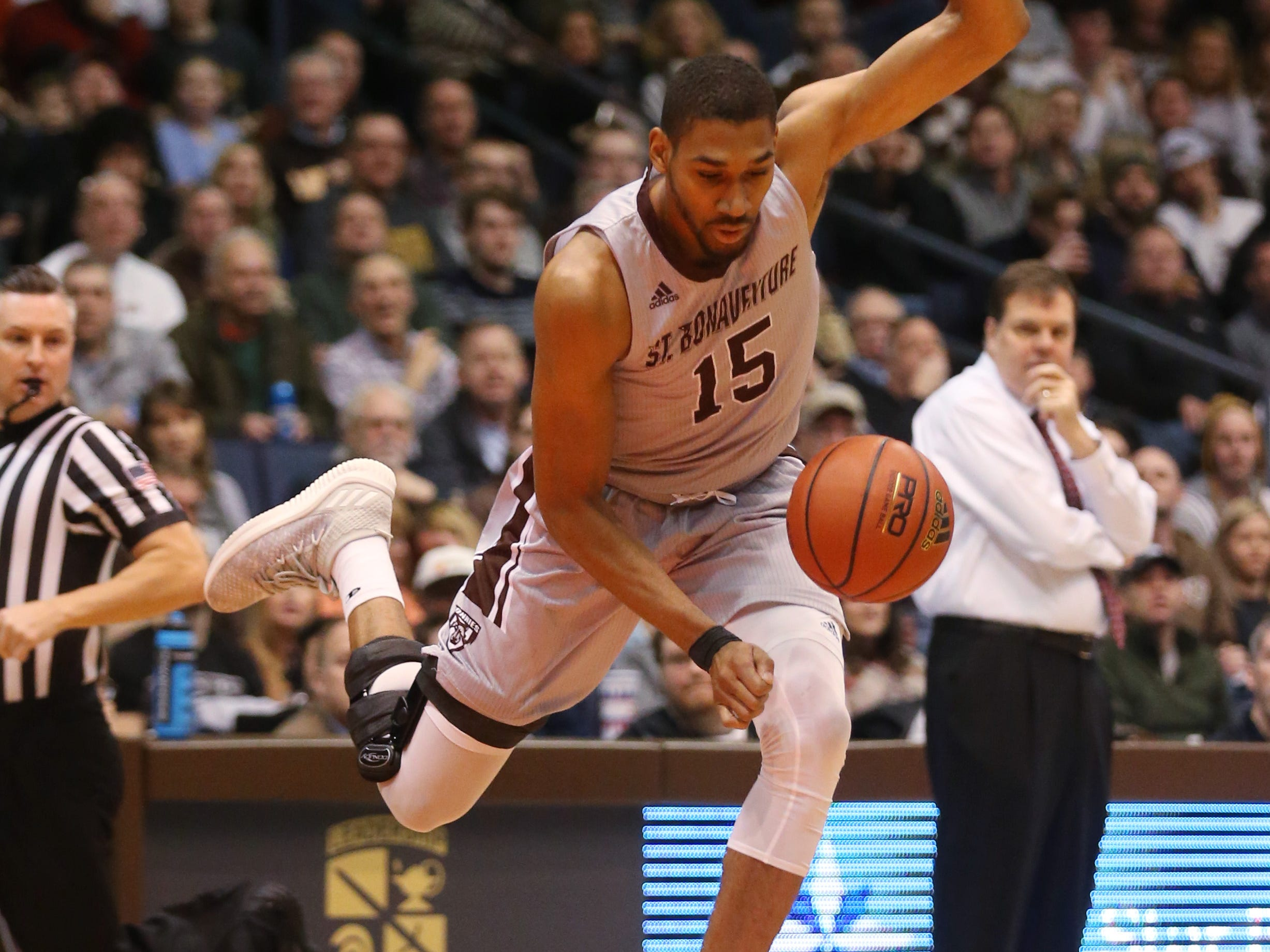 St. Bonaventure's LaDarien Griffin leaps over Fordham's diving Nick Honor as he steals the ball during the first half.
