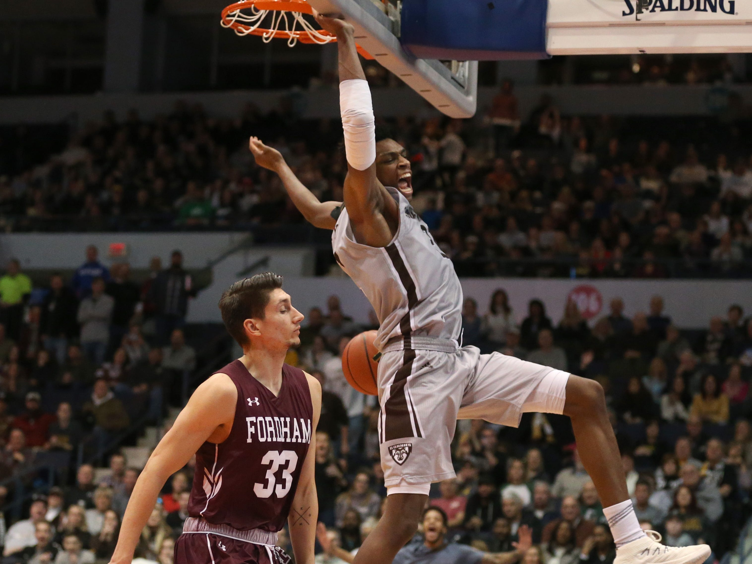 St. Bonaventure's Osun Osunniyi slams home the final two points of the game as he outraces Fordham's David Pekarek to the basket.