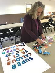 Kay Johnson of Redding puts together letters for a sign intended for Saturday's Women's March in Redding.