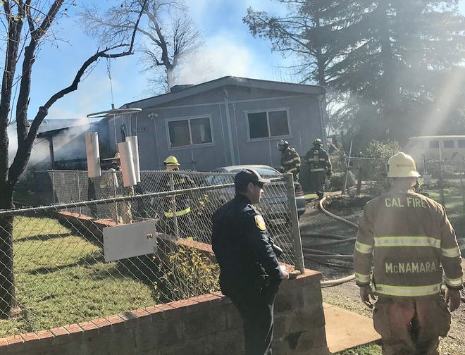 Firefighters work on a home that caught fire Sunday morning. One person was arrested after firefighters and Shasta County Sheriff's deputies arrived.