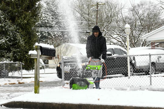 Nathan Showell clears snow that coats the sidewalks in Salisbury on Sunday, Jan. 13, 2019.