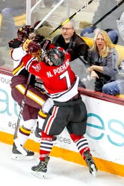 Defenseman Scott Perunovich (7) of the Minnesota Duluth Bulldogs and forward Nick Poehling (7) of the St. Cloud State Huskies fight during Saturday's game at Amsoil Arena in Duluth, Minn.