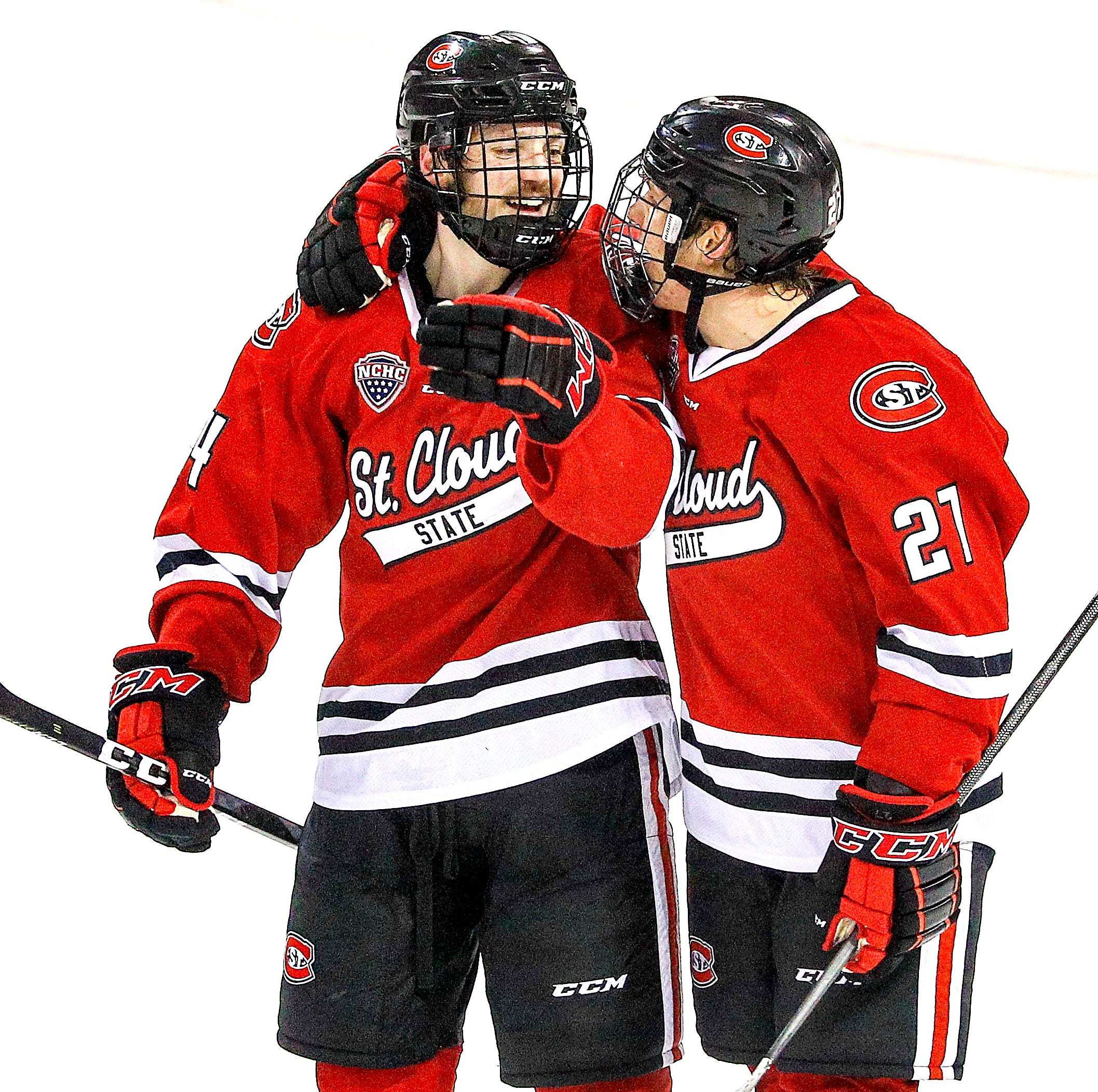 Patrick Newell (14) and Blake Lizotte of the St. Cloud State Huskies celebrate a late third period goal during Saturday's game at Amsoil Arena in Duluth, Minn.