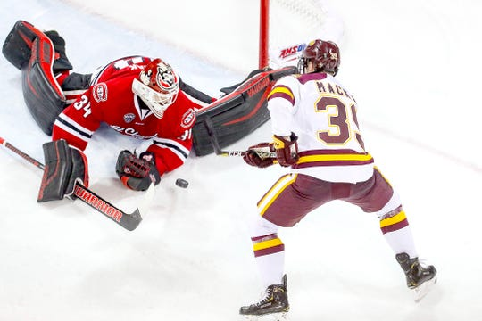 Forward Parker Mackay (39) of the Minnesota Duluth Bulldogs shoot the puck on net against goaltender Dávid Hrenák (34) of the St. Cloud State Huskies during Saturday's game at Amsoil Arena in Duluth, Minn.