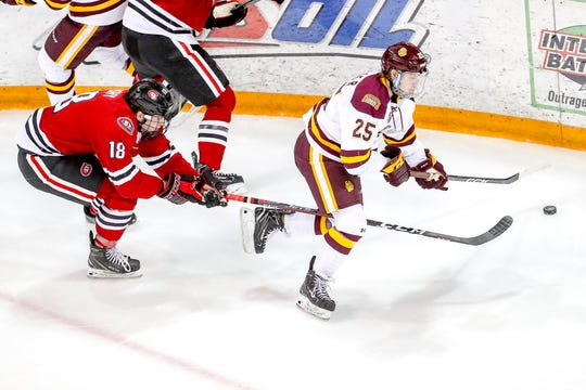 Defenseman Brendan Bushy (18) of the St. Cloud State Huskies pushes his stick though the legs of forward Peter Krieger (25) of the Minnesota Duluth Bulldogsduring Saturday's game at Amsoil Arena in Duluth, Minn.