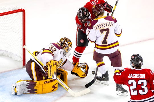 Goaltender Hunter Shepard (32) of the Minnesota Duluth Bulldogs stops the puck from forward Sam Hentges (19) of the St. Cloud State Huskies during Saturday's game at Amsoil Arena in Duluth, Minn.