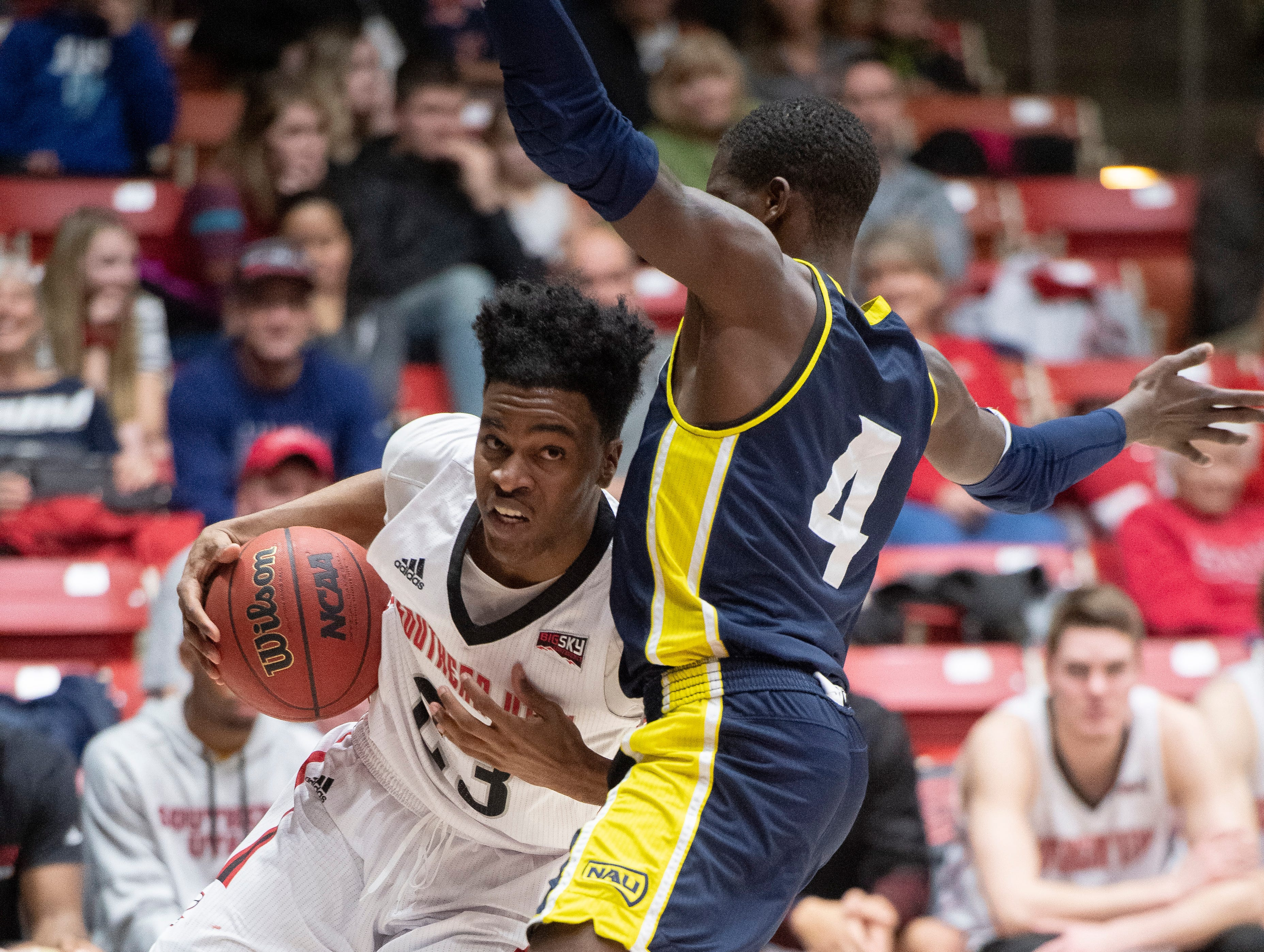 Southern Utah University junior Cameron Oluyitan (23) tries to get around a Northern Arizona defender at the America First Event Center Saturday, January 12, 2019. SUU won, 84-82.