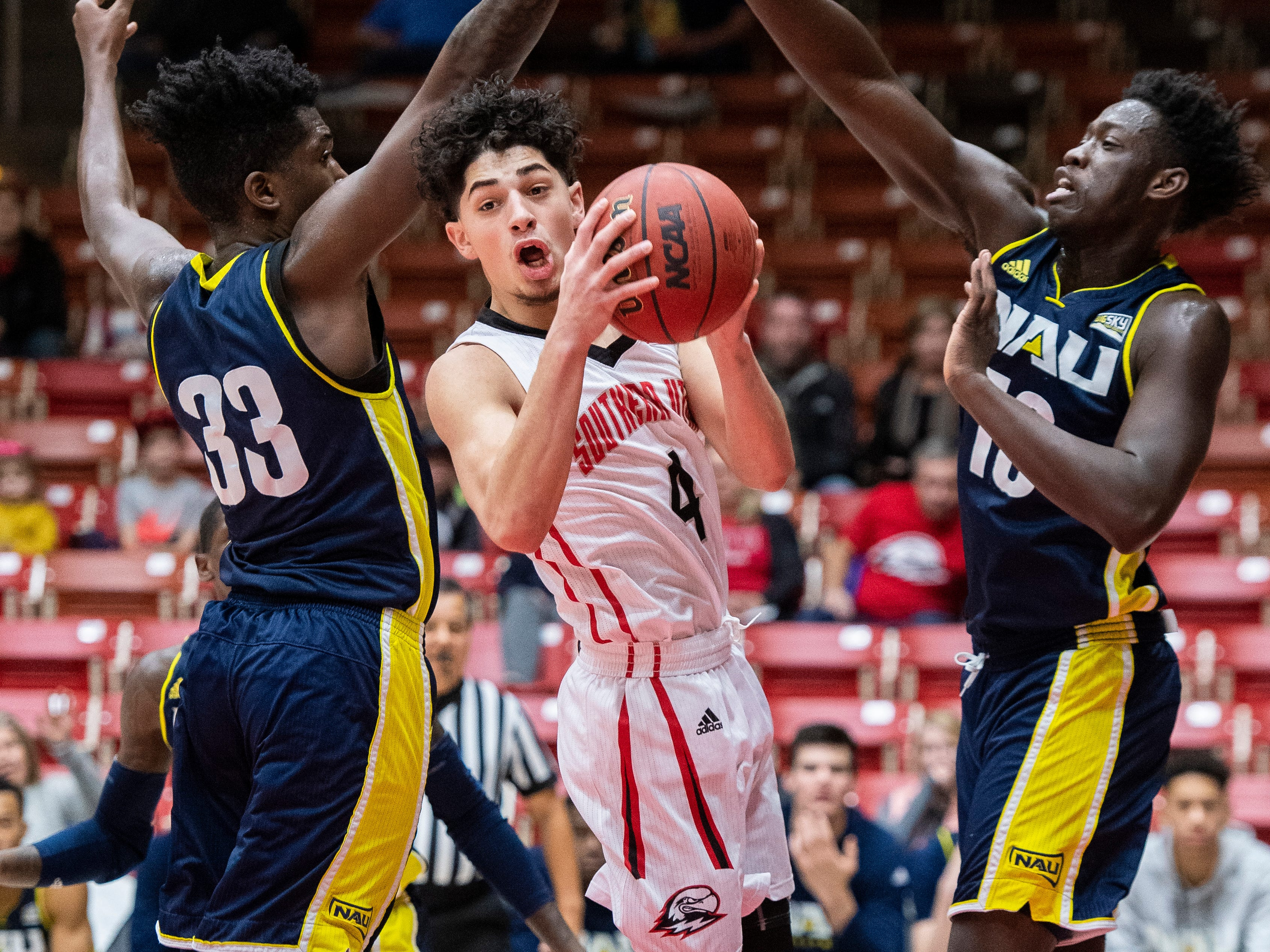 Southern Utah University sophomore Dre Marin (4) sneaks through the Nothern Arizona defense to throw a pass at the America First Event Center Saturday, January 12, 2019. Thanks to Marin scoring a buzzer-beater, SUU won, 84-82.