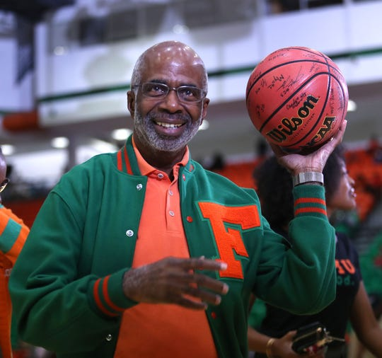 FAMU President Dr. Larry Robinson received an autographed basketball from players on both teams as a birthday present.
