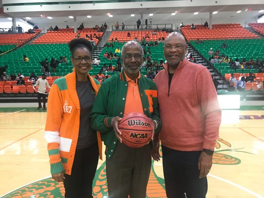 FAMU president Dr. Larry Robinson (center) shares a moment with his wife, Sharon, and athletics director Dr. John Eason. Robinson was presented with an autographed basketball as a birthday present during halftime of the men's game versus Savannah State.