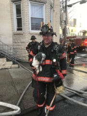 Firefighter Brendan Healy with a dog that the Yonkers Fire Department rescued from a fire.
