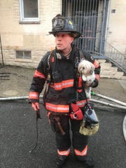 Lieutenant Steve Trizano with a dog that the Yonkers Fire Department rescued from a fire.