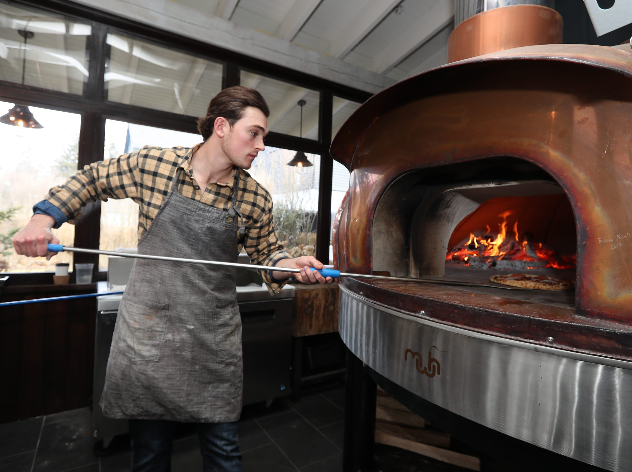 Pizza chef Chase Fox Harnett pulls a pizza from the wood fired oven at the Valley Rock Inn & Mountain Club in Sloatsburg on Saturday, January 12, 2019.