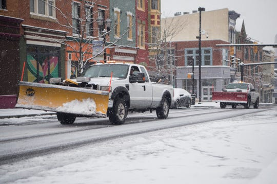 Plow trucks make their way down Market Street Sunday morning.