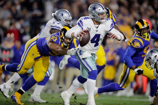 Dallas Cowboys quarterback Dak Prescott breaks away from Los Angeles Rams nose tackle Ndamukong Suh during the first half in an NFL divisional football playoff game Saturday, Jan. 12, 2019, in Los Angeles.