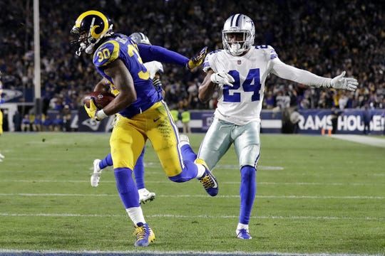 Los Angeles Rams running back Todd Gurley scores past Dallas Cowboys cornerback Chidobe Awuzie during the first half in an NFL divisional football playoff game Saturday, Jan. 12, 2019, in Los Angeles.