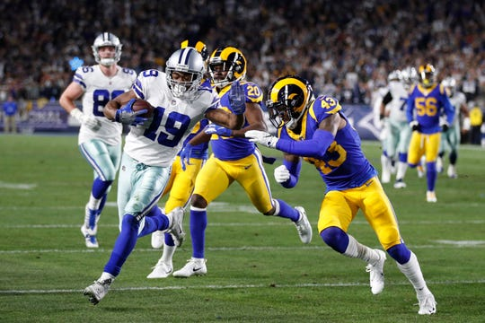 Dallas Cowboys wide receiver Amari Cooper, left, scores past Los Angeles Rams strong safety John Johnson during the first half in an NFL divisional football playoff game Saturday, Jan. 12, 2019, in Los Angeles.