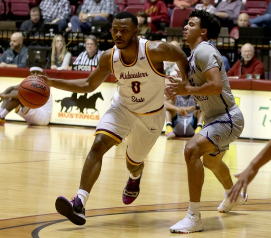 Midwestern State's JaJuan Starks dribbles by Western New Mexico's Eddie Giron Saturday, Jan. 12, 2019, in D.L. Ligon Coliseum.