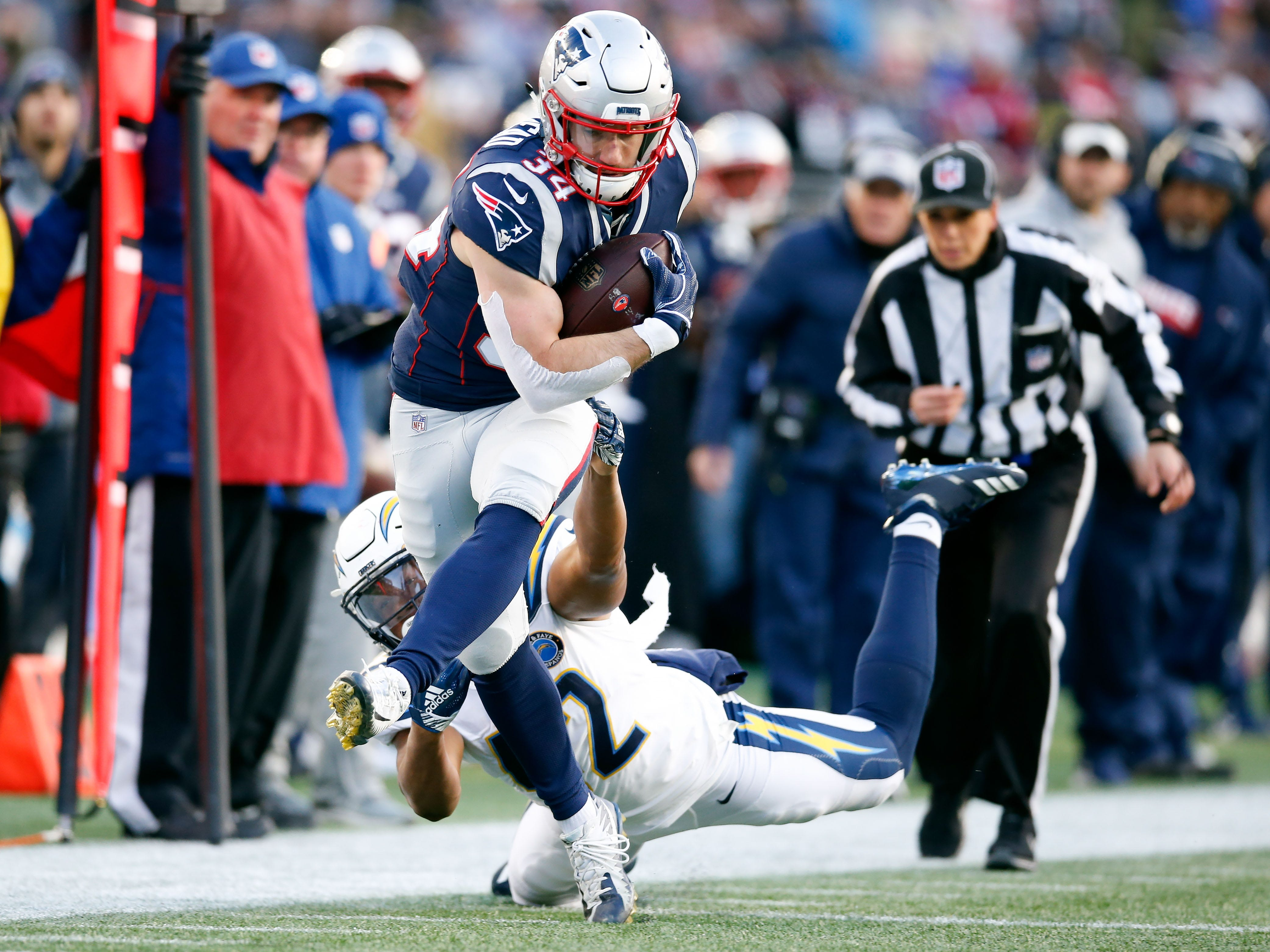 New England Patriots running back Rex Burkhead (34) runs against Los Angeles Chargers linebacker Uchenna Nwosu (42) during the third quarter in an AFC Divisional playoff football game at Gillette Stadium.