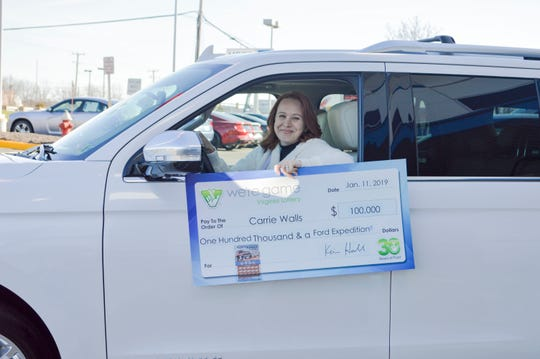 Carrie Walls of Ashburn, Virginia, shows her lucky new earnings while riding the SUV she also won in the lottery.
