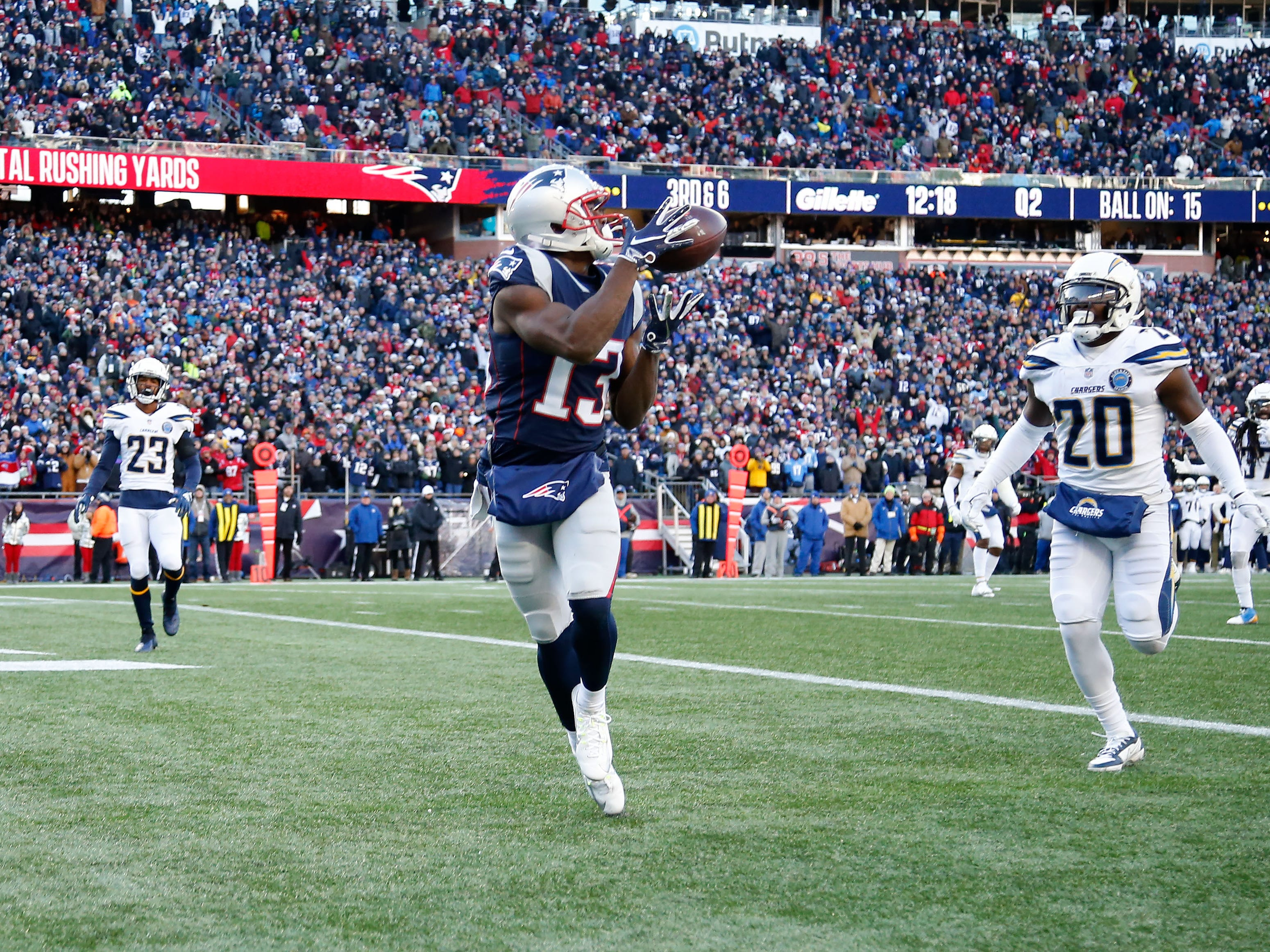 New England Patriots wide receiver Phillip Dorsett (13) catches a pass for a touchdown in front of Los Angeles Chargers defensive back Desmond King (20) during the second quarter in an AFC Divisional playoff football game at Gillette Stadium.
