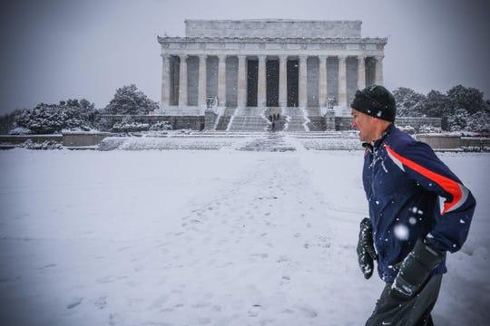 A jogger runs by the Lincoln Memorial as snow accumulates in Washington, D.C., on Jan. 13, 2019.