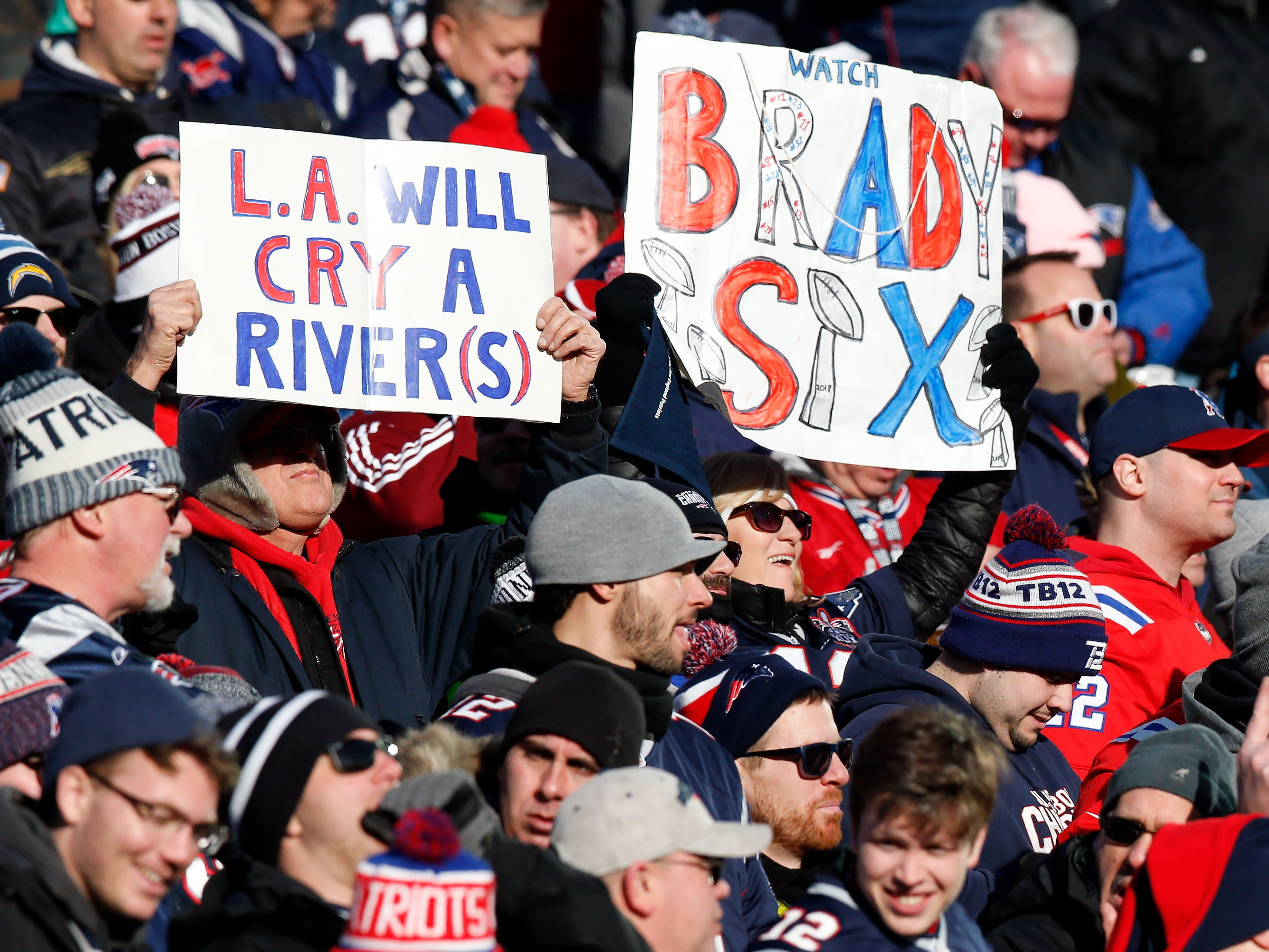 New England Patriots fans hold up signs during the AFC divisional playoff game against the Los Angeles Chargers at Gillette Stadium.