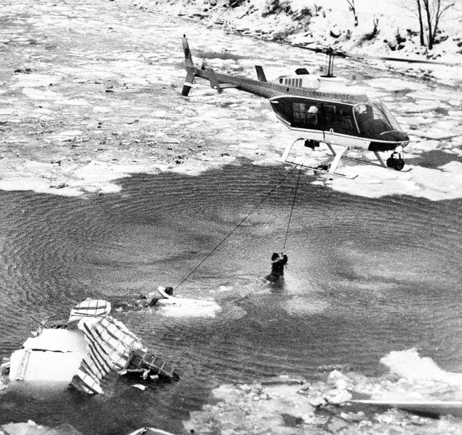 A U.S. Park Police helicopter pulls two people from the wreckage of an Air Florida jetliner that crashed into the Potomac River when it hit a bridge after taking off from National Airport in Washington, D.C., on Jan. 13, 1982.