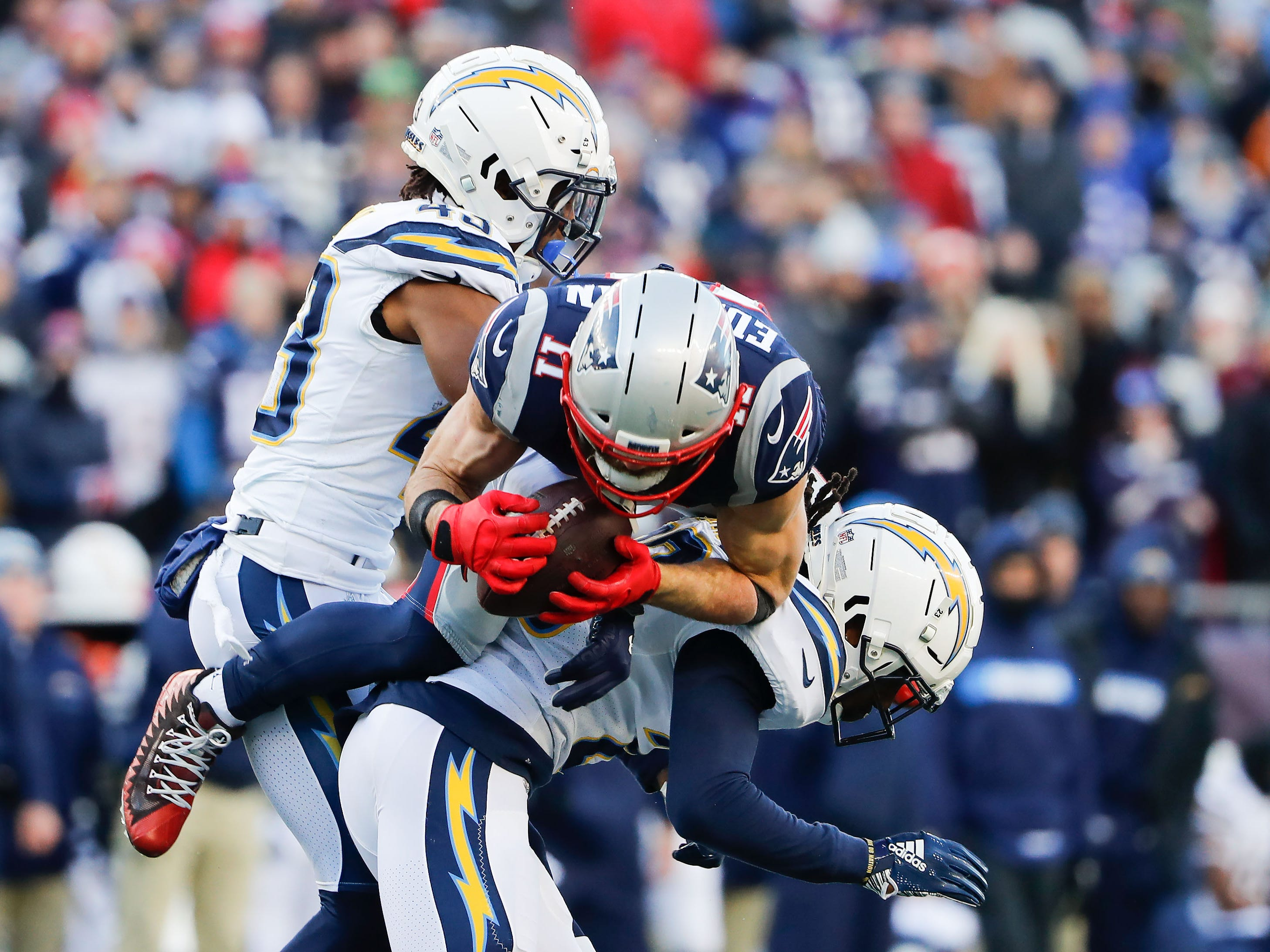 New England Patriots wide receiver Julian Edelman (11) dives over Los Angeles Chargers defensive back Rayshawn Jenkins (23) during the second quarter in an AFC Divisional playoff football game at Gillette Stadium.