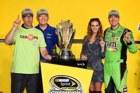 J.D. Gibbs, left, celebrates with father Joe Gibbs, Samantha Busch and driver Kyle Busch after Busch won the 2015 NASCAR Cup Series championship.
